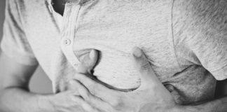 Man hält sich an der Brust