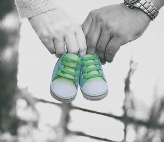 Eltern halten Babyschuhe in den Händen